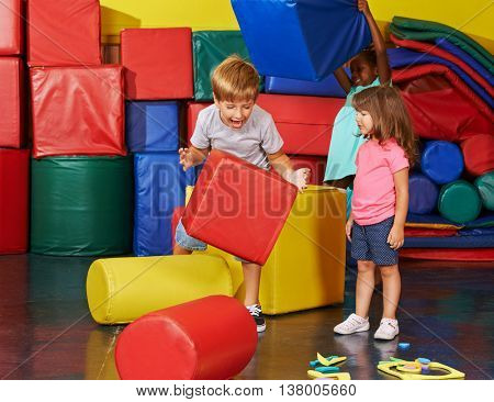 Happy children playing together in gym of a preschool