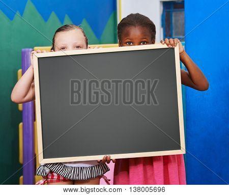 Two children holding an empty blackboard in a preschool
