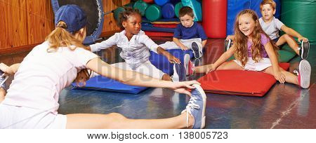 Children doing gymnastics in gym of preschool with nursery teacher