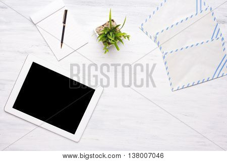 Top view of a tablet computer and office items on a white wooden desk. Home office concept. Business and lifestyle. Copyspace.