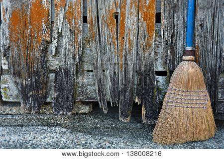 Used broom with blue handle leaning on dilapidated barn.