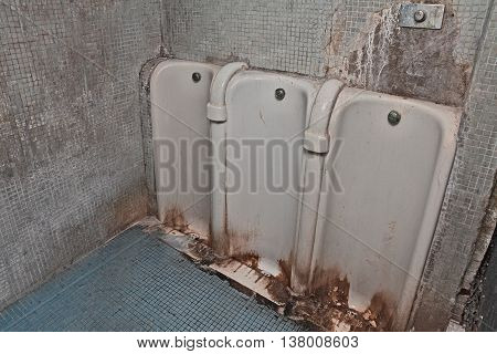 public restroom with dirty and fouling old urinals