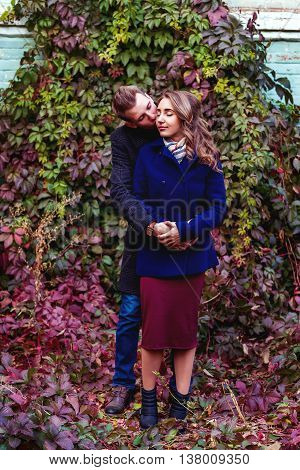 Couple kissing near hedge with colorful leaves