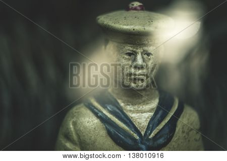 Portrait of a sailor figurine photographed in Odessa through the glass funiture in the store, the old Russian manipulative optics.