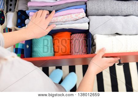 Woman folding clothes into chest of drawers closeup