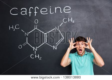 Funny crazy young professor of chemistry standing and shouting over chalkboard background