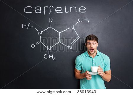 Surprised young student drinking coffee over drawn chemical structure of caffeine molecule on blackboard