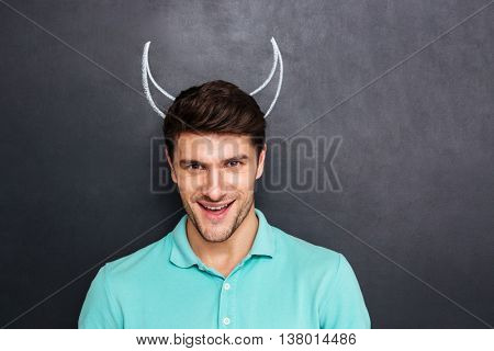 Portrait of smiling young man with drawn devil horns over chalkboard background