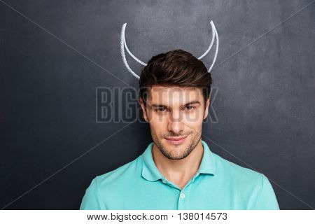 Closeup of handsome young man with drawn devil horns over blackboard background
