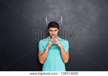 Serious young man playing role of devil standing over blackboard background with drawn horns