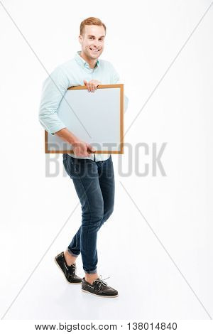Full length of cheerful african young man walking and holding whiteboard