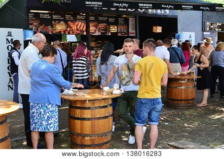 CLUJ-NAPOCA ROMANIA - JULY 9 2016: People eat fast food at the Street Food Festival in central park Cluj. Vendors in stalls sell tasty fast food from different cultures.