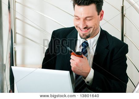 Businessman working at home with his laptop sitting on the stairs in his apartment