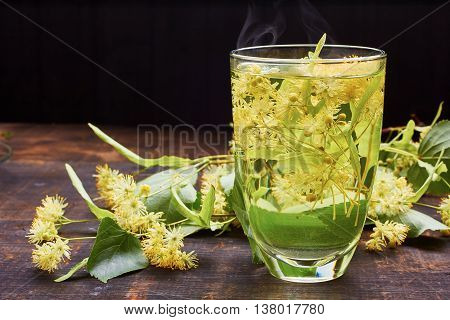 Glass of hot linden tea with fresh flowers on dark wooden background
