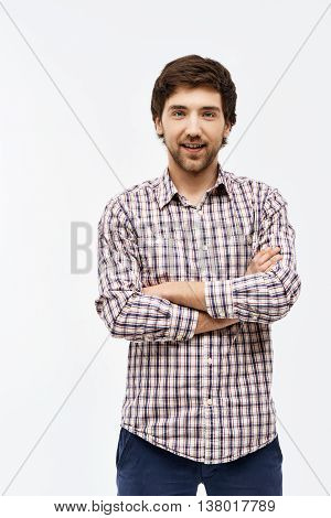 Close-up portrait of handsome confident young blue-eyed dark-haired man with arms crossed on chest wearing casual plaid shirt and jeans looking at camera. Isolated on white background.