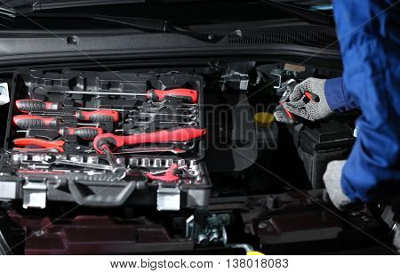 Professional auto mechanic working in repairing service, close-up. Car diagnostics concept