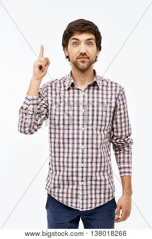 Close-up portrait of handsome confident young blue-eyed dark-haired man wearing casual plaid shirt and jeans looking at camera, pointing up. Isolated on white background.