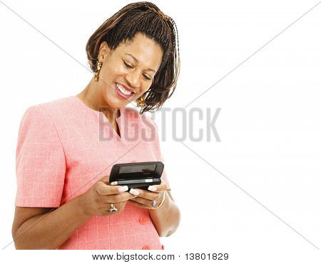 Pretty african-american woman sending a text message on her smart phone.  Isolated on white.