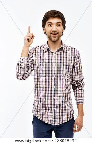 Close-up portrait of handsome smiling young blue-eyed dark-haired man wearing casual plaid shirt and jeans looking at camera, pointing upward. Isolated on white background.