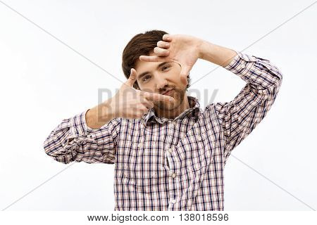 Close-up portrait of handsome confident young blue-eyed dark-haired man wearing casual plaid shirt looking at camera making frame with his hands. Isolated on white background.