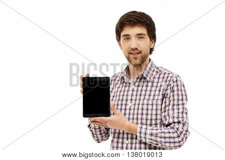 Close-up portrait of handsome confident young blue-eyed dark-haired man wearing casual plaid shirt showing tablet screen. Isolated on white background.