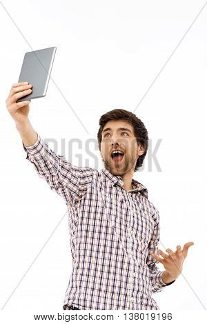 Close-up portrait of handsome smiling young blue-eyed dark-haired man wearing casual plaid shirt having fun making selfie with tablet in one hand. Isolated on white background.
