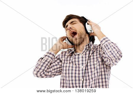 Close-up portrait of handsome romantic young blue-eyed dark-haired man wearing casual plaid shirt singing in head phones. Emotional. Isolated.