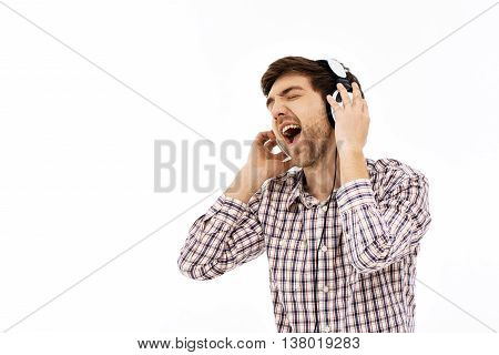 Close-up portrait of handsome romantic young blue-eyed dark-haired man wearing casual plaid shirt singing in head phones. Emotional happy face. Isolated.
