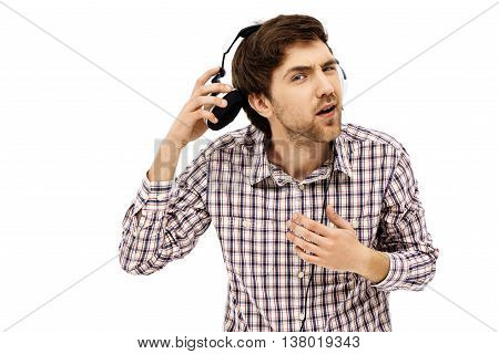 Close-up portrait of handsome young blue-eyed dark-haired man wearing casual plaid shirt in head phones. Emotional surprised face. Isolated.