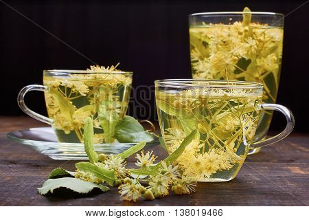 Group of glass cups of linden tea with fresh flowers on dark wooden background.