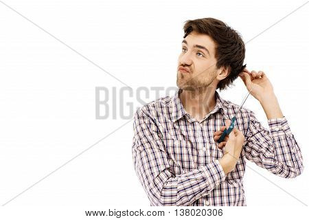 Close-up portrait of handsome confident young blue-eyed dark-haired man cutting hair with scissors wearing casual plaid shirt. Isolated.