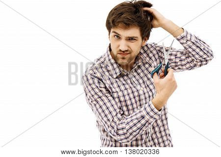 Close-up portrait of handsome curious young blue-eyed dark-haired man cutting hair with scissors wearing casual plaid shirt. Isolated.
