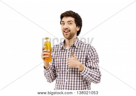 Young handsome cheerful man in plaid shirt holding plastic bottle with orange beverage showing thumb up. Looking at camera. Isolated on white background.