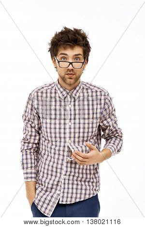 Crazy and funny surprised handsome young man in jeans, plaid shirt and glasses with messy hair looking at camera. Isolated on white background.