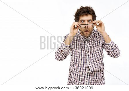 Crazy and funny shocked handsome young man in plaid shirt and glasses with messy hair. Isolated on white background.