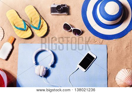 Summer vacation composition with a pair of yellow flip flop sandals, hat, sunglasses, sun cream and other stuff on a beach. Sand background, studio shot, flat lay.