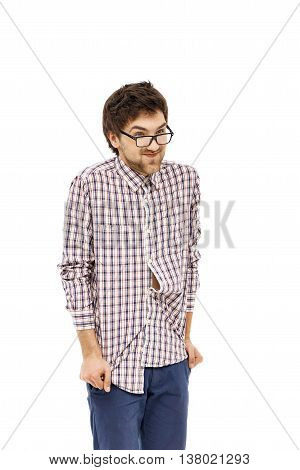 Crazy and funny handsome young man in plaid shirt and glasses with messy hair putting hands in pockets of his jeans. Isolated on white background.