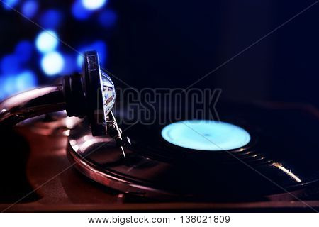 Turntable with vinyl record on dark blurred background
