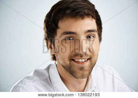 Close up portrait of smiling elegant confident handsome young businessman in white shirt looking at camera. Studio, isolated on grey background.