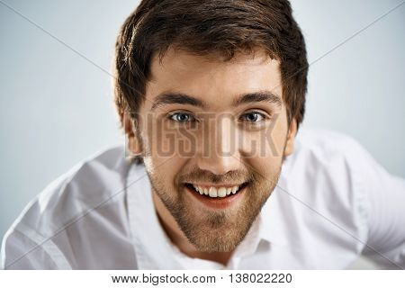 Close up portrait of smiling elegant cheerful handsome young businessman in white shirt looking at camera. Studio, isolated on grey background.