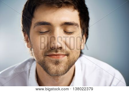 Close up portrait of relaxed elegant handsome young businessman in white shirt with closed eyes. Studio, isolated on grey background.