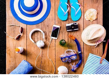 Summer vacation composition with smart phone, camera, pair of flip flop sandals, hat, sunglasses, sun cream and other stuff on a wooden background, studio shot, flat lay.