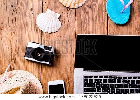 Summer vacation composition with laptop, camera, smart phone, blue flip flop sandals, hat and other stuff on wooden background, studio shot, flat lay.