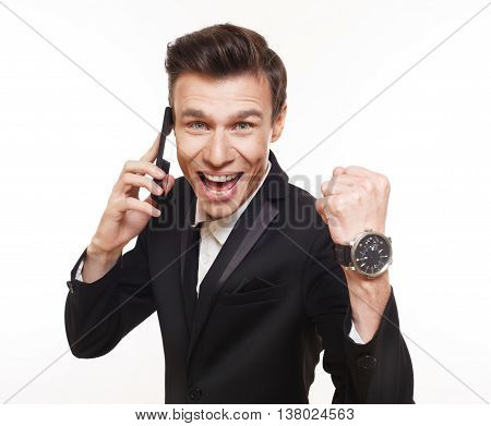 Happy man with mobile phone, success concept. Connection, communication. Emotional guy in suit isolated at white celebrates victory, lucky winner concept
