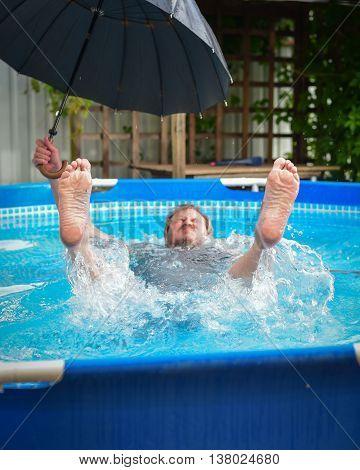 man in the pool during a rain under an umbrella