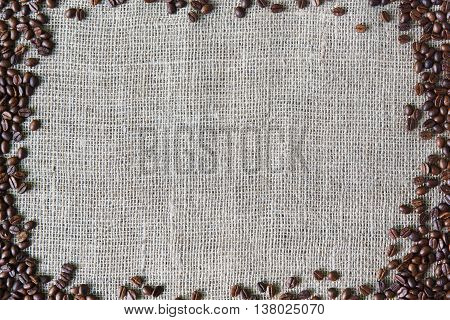 Burlap texture with coffee beans border. Sack cloth background. Brown natural sackcloth canvas with frame and copy space. Seeds at hessian textile