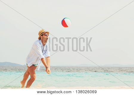 Young handsome man playing on the beach with a ball
