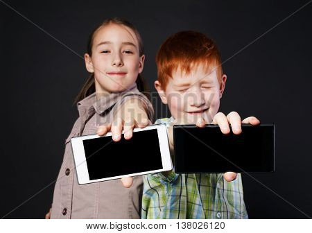 Portrait of happy, smiling girl and unhappy boy, children show mobile phone with screen for copyspace at black background. Positive and negative facial expression, emotions. New generation gadgets