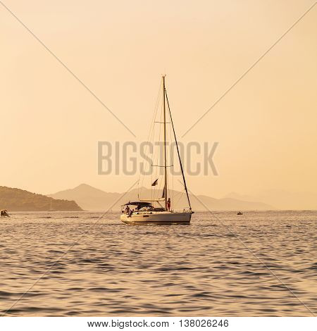 Luxury yacht sails on the Adriatic Sea coastline. Traveling near the island. The boat is sailing into the port at sunset. Dubrovnik, Croatia