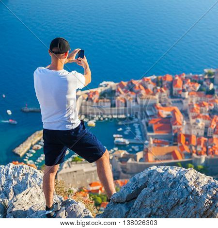 Male traveller make a panoramic photo of the old city of Dubrovnik from the mountain to his phone for Instagram or other social networks. Travel to Croatia. Summer vacation.